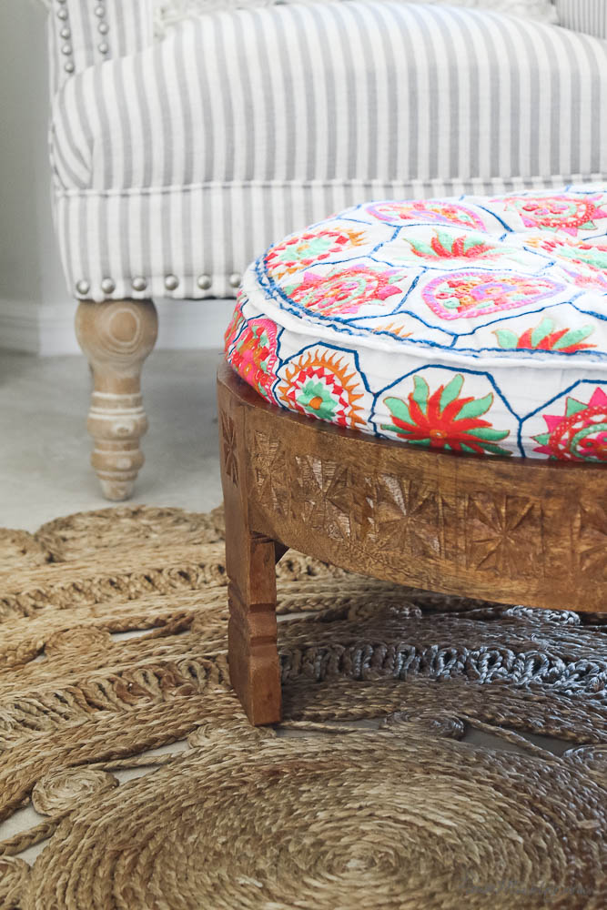 colorful ottoman with neon colors and carved wooden base