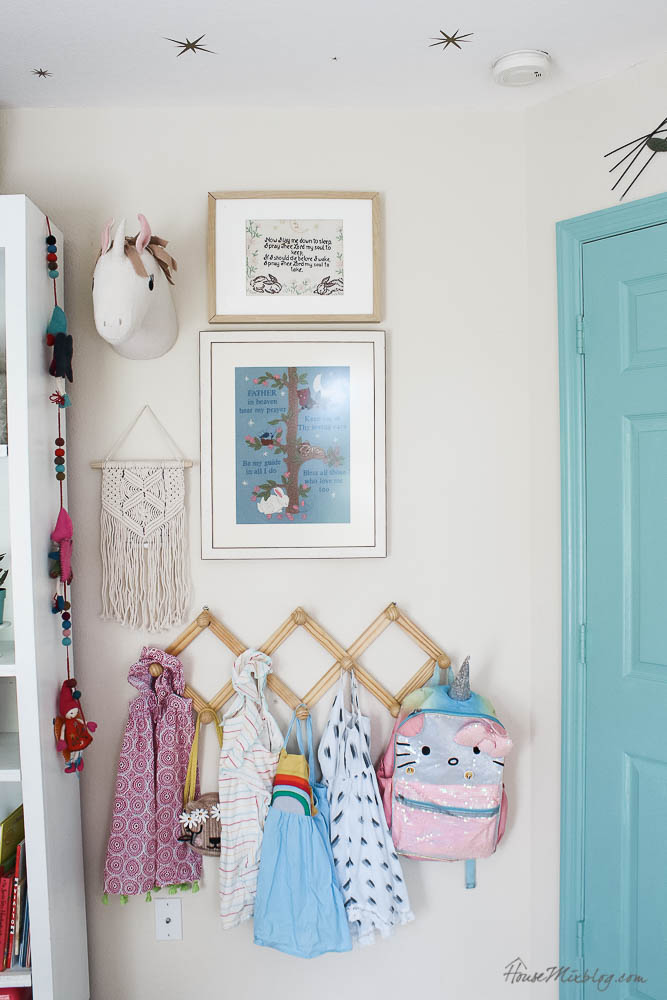Book shelves styling in girls room with art - accordion hooks to hang dresses