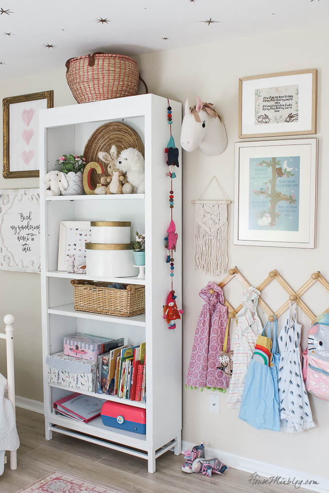 Book shelves styling in girls room with art