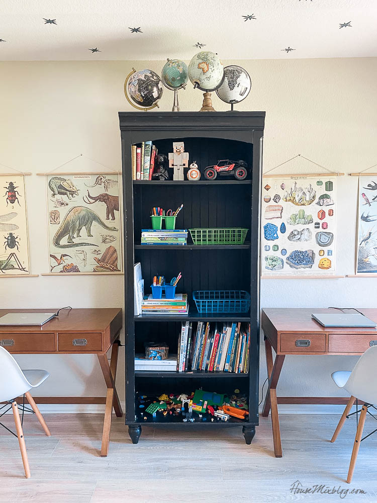 boys shared work stations with wood desks, vintage posters and globes