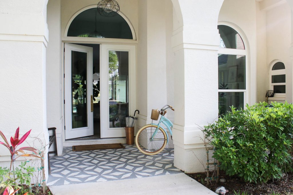 White front door with gold handle and arch window