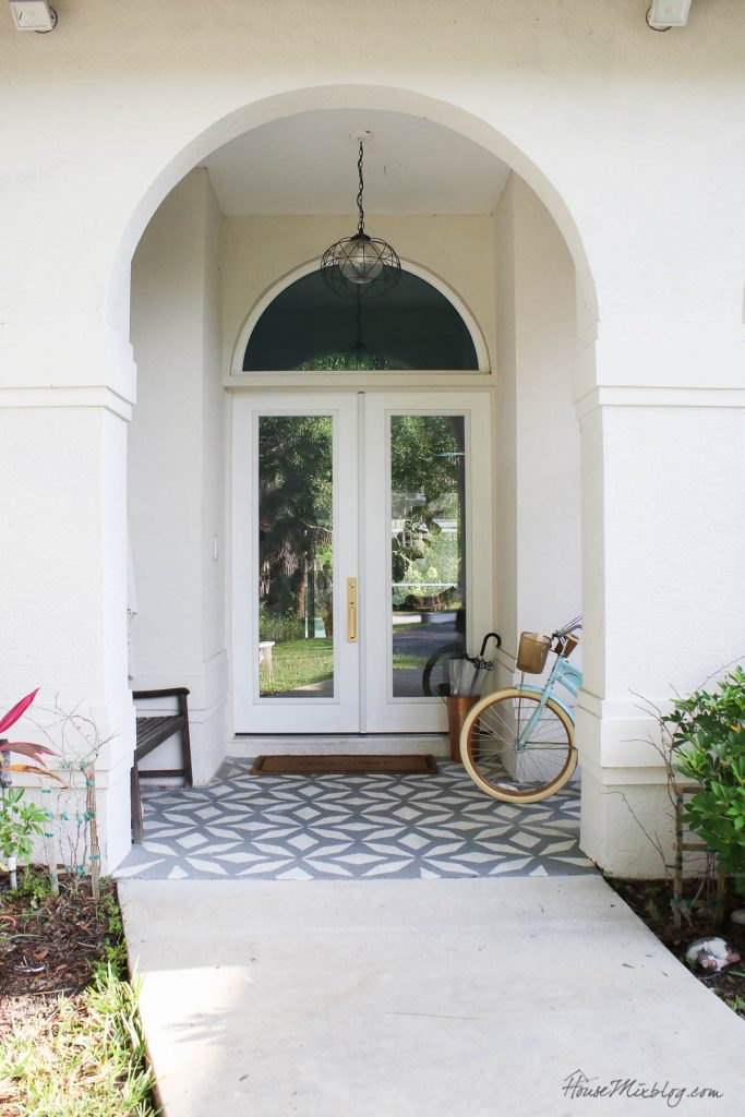 White front door with arch, stenciled patio and gold handle set