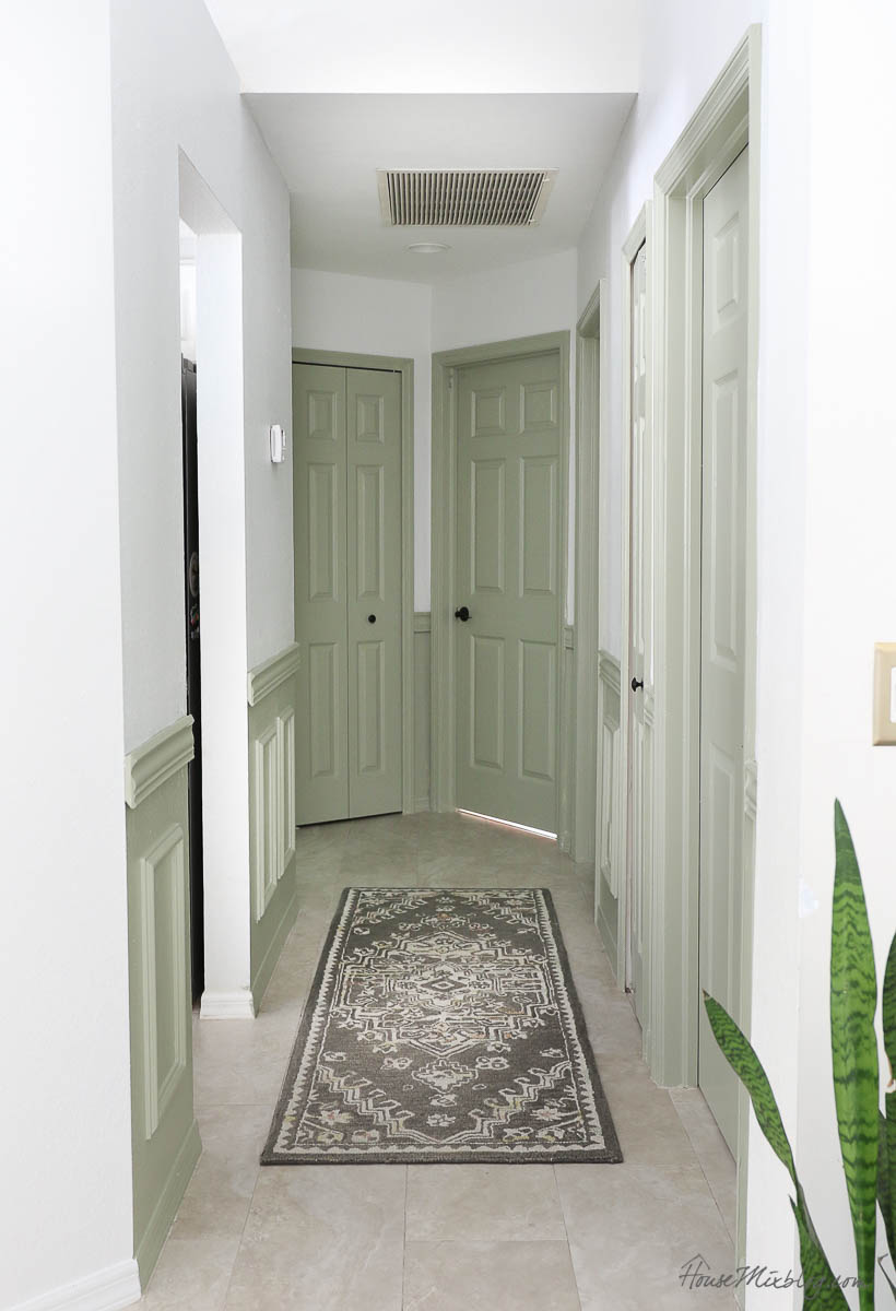 Sage doors and wainscoting trim in hallway with black hinges and handles - paper white walls