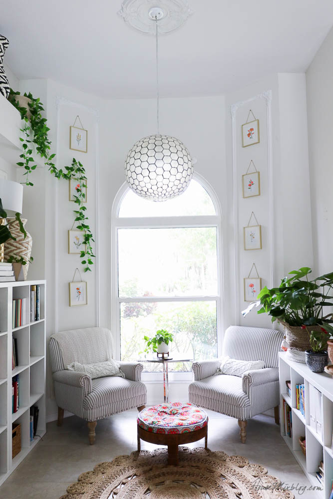 White reading nook with bookshelves and plants